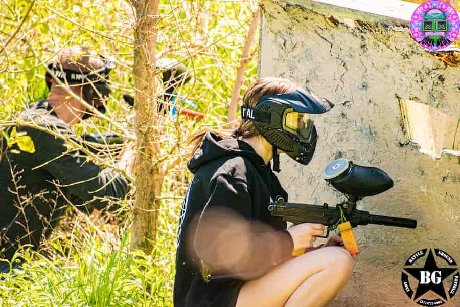 two players crouching on paintball field at company event