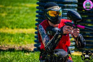 indianapolis paintball player crouching by tires